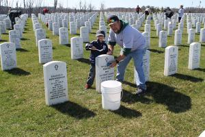 The MCO's Military Members committee cleans veteran's headstones in spring 2016. MCO has many members that volunteer in their communities.